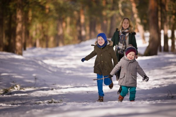 Happy family walking in a winter forest. Young woman, cute toddler boy and kid boy smiling and running on the snow on a sunny day.