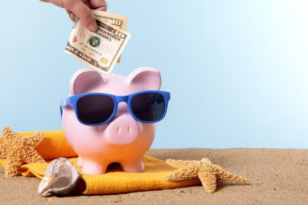 Saving for beach vacation, with pink piggy bank and sunglasses.  Studio shot with plain blue background.  Sharp focus on the ten dollar bill.  Space for copy.  Warm color and directional lighting are intentional.